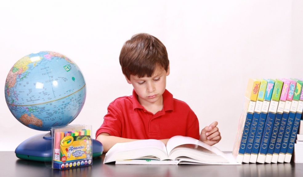 Boy being home educated at desk with globe and educational books
