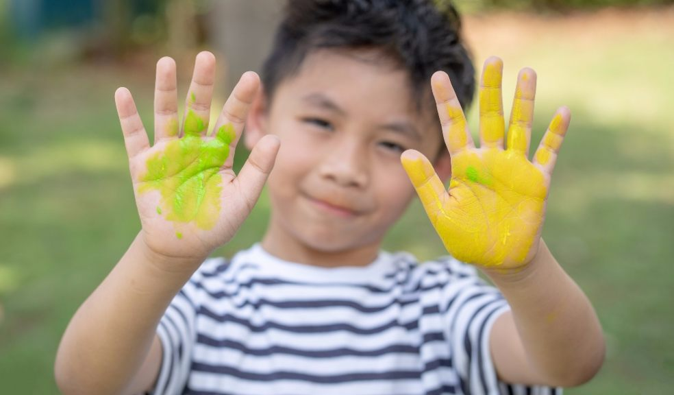Happy funny child draws laughing shows hands dirty with paint. Family.