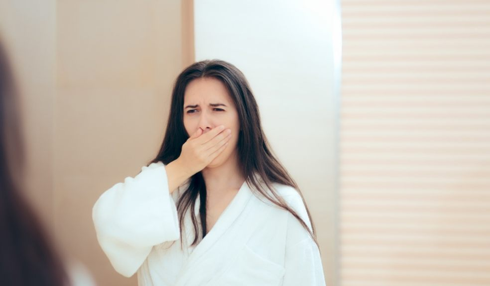 Woman in robe feeling tired after not enough sleep