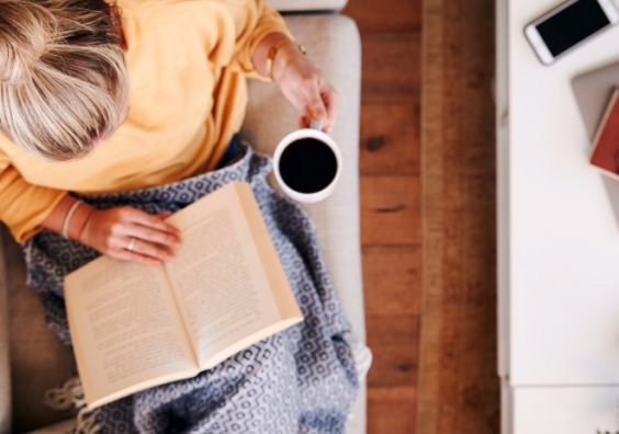 Woman reading book on sofa with a cup of coffee. Getty Images/iStockphoto