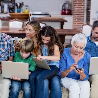 Family on laptops, tablets and mobile phones