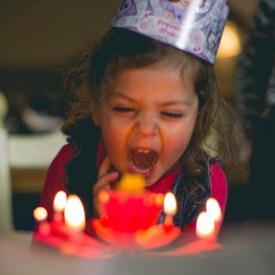 little girl blowing out candles on family birthday party